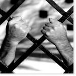 Des mains derrière les barreaux